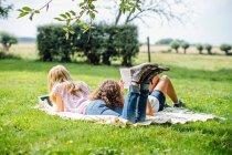 Дві дівчинки підлітка лежав у саду читання і використовуючи цифровий планшетний — стокове фото