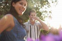 Coppie in giardino, uomo che beve il bicchiere d'acqua — Foto stock