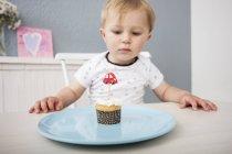Bambino ragazzo guardando cupcake — Foto stock