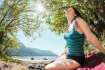 Mulher sentada à beira lago rural a sorrir — Fotografia de Stock