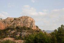 Formações rochosas no topo de uma colina rural com abetos — Fotografia de Stock