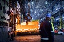 Steelworker inspects steel in furnace in steelworks — Stock Photo