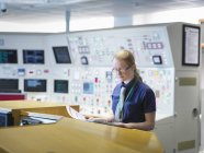 Female operator reading notes in nuclear power station control room simulator — Stock Photo