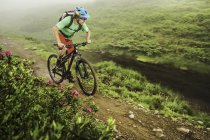 Young male mountain biker cycling next to stream — Stock Photo