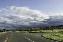 Vista de carretera con campos verdes y un cielo nublado - foto de stock