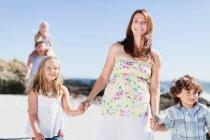Madre e bambini camminano sulla spiaggia — Foto stock