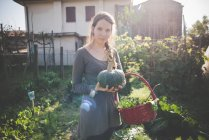 Young woman holding homegrown squash — Stock Photo