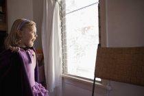 Retrato de jovem olhando pela janela — Fotografia de Stock
