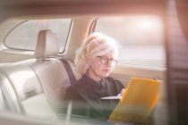Mature businesswoman, sitting in car, looking at documents — Stock Photo