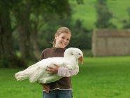 Girl Holding Big Goose outdoors — стоковое фото