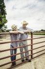 Agricultor e neto adolescente inclinando-se contra bate-papo portão — Fotografia de Stock