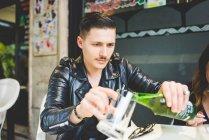 Мужчина наливает пиво в кружку в кафе на тротуаре — стоковое фото