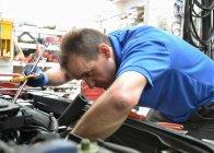 Механик среднего возраста, проверяющий двигатель автомобиля — стоковое фото