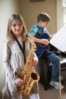 Lächelndes Mädchen spielt Saxofon — Stockfoto