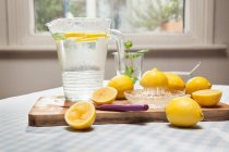 Lemons, juicer and pitcher of water — Stock Photo