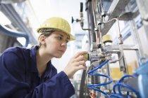 Женщина-инженер проверяет кабели на промышленном оборудовании — стоковое фото