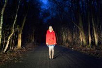 Woman standing on road in woods at night — Stock Photo