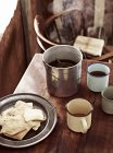 Rustic table with billycan tea and biscuits — Stock Photo