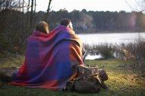 Молодая пара на озера, завернутый в одеяло на закате — стоковое фото