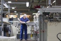 Рабочий, использующий машину на бумажной упаковке — стоковое фото