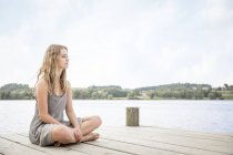 Portrait of young woman sitting on jetty, crossed legs — Stock Photo