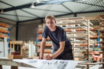 Portrait of young male carpenter at workbench — Stock Photo