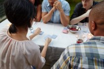 People playing card game at garden — Stock Photo