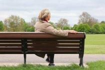 Haute femme assis sur un banc de parc, vue arrière — Photo de stock