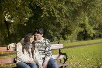 Giovane coppia seduta sulla panchina del parco — Foto stock