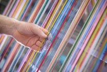 Працівник, регулюючи багатобарвні шовкової пряжі на промислових Ткацький верстат на текстильна фабрика — стокове фото