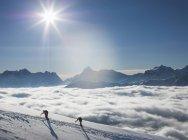 Zwei Bergsteiger an einem schneebedeckten Hang über einem Nebelmeer in einem Alpental, Alpen, Kanton Wallis, Schweiz — Stockfoto