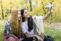 Giovani donne che si fanno selfie nella foresta, Hampstead Heath, Londra — Foto stock