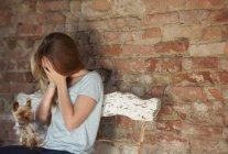 Adolescente chorando e sentado no banco com o cão — Fotografia de Stock