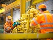 Жіночі та чоловічі інженери, що працюють на движку — стокове фото
