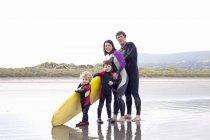 Famiglia con due ragazzi e tavola da surf in spiaggia — Foto stock