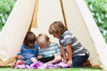 Jungen nutzen Tablet-Computer im Zelt — Stockfoto