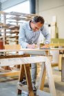 Mature male carpenter drawing blueprint in workshop — Stock Photo