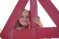 Ritratto di ragazza che guarda attraverso il triangolo rosso — Foto stock