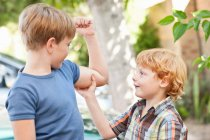 Мальчик чувствует братья бицепсы на открытом воздухе — стоковое фото