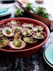Pan of oysters floating in water — Stock Photo