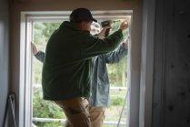 Hijo adulto con padre instalando nueva ventana en el sitio de construcción de la casa - foto de stock