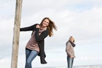 Woman swinging from pole on beach — Stock Photo