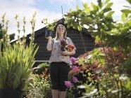 Женщина, держа растений в садовый центр — стоковое фото