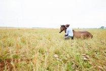 Женщина на корточках с рукой вокруг лошади, лежа в поле — стоковое фото