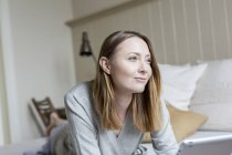 Ritratto di donna distesa sul davanti sul letto mentre distoglie lo sguardo sorridente — Foto stock