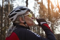 Side view of woman wearing cycling helmet and sunglasses drinking water from plastic bottle — Stock Photo