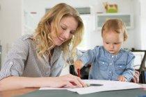 Девочка рисует с мамой дома — стоковое фото