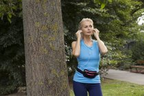 Mature woman adjusting earphones whilst training in park — Stock Photo