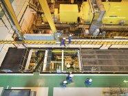 Trabajadores en la sala de turbinas de la central eléctrica, vista de ángulo alto - foto de stock