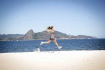 Young woman jumping on beach, Rio de Janeiro, Brazil — Stock Photo